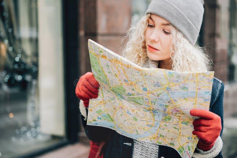 Jonge blonde krullende vrouwelijke toerist met kaart stock foto