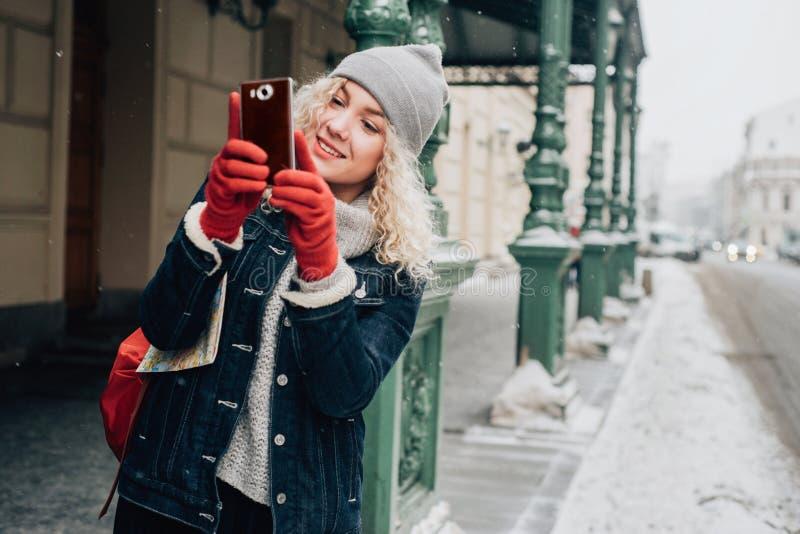 Jonge blonde krullende vrouwelijke toerist in warme kleren royalty-vrije stock fotografie