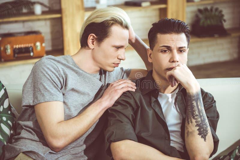 Jonge blonde mens wat betreft schouder van zijn droevige vriend stock fotografie