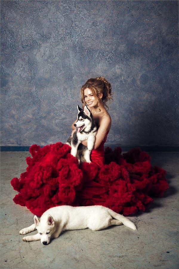 Jonge blonde mooie jonge vrouw die huskies puppyhond koesteren stock afbeeldingen