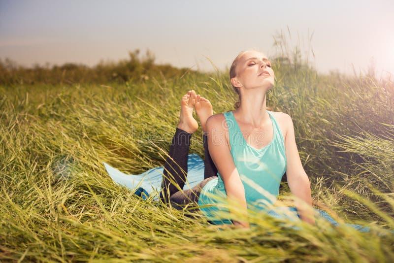 Jonge blonde mooie vrouw die yogaoefeningen op het gras doen stock fotografie