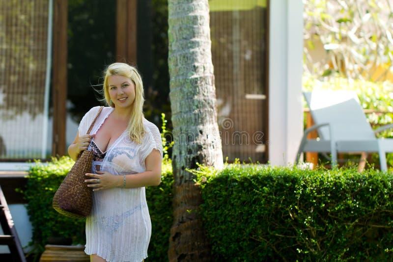 Jonge blonde mooie vrouw in doorschijnende strandkleding en bikini dichtbij luxe tropische villa met grote zak die gaan aan stock foto's