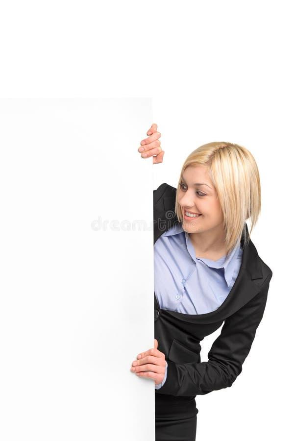 Jonge blonde onderneemster die witte banner bekijkt stock afbeeldingen