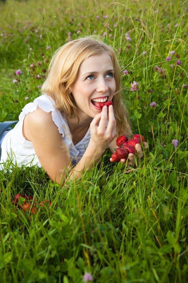 Jonge blonde vrouw die aardbeien eet stock foto's