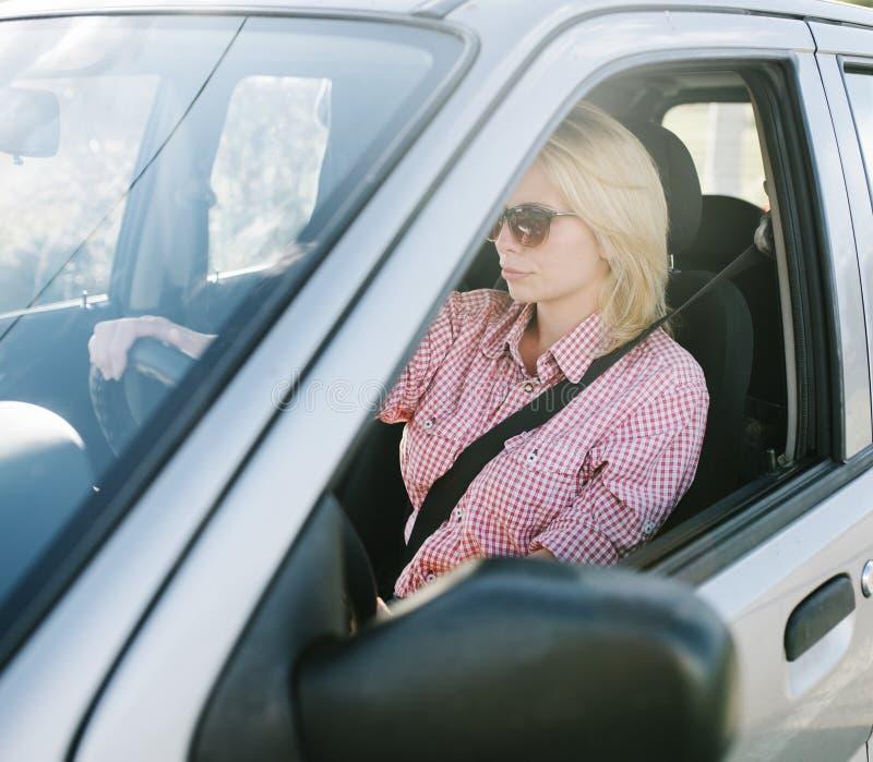Jonge blonde vrouw die een auto drijft royalty-vrije stock foto