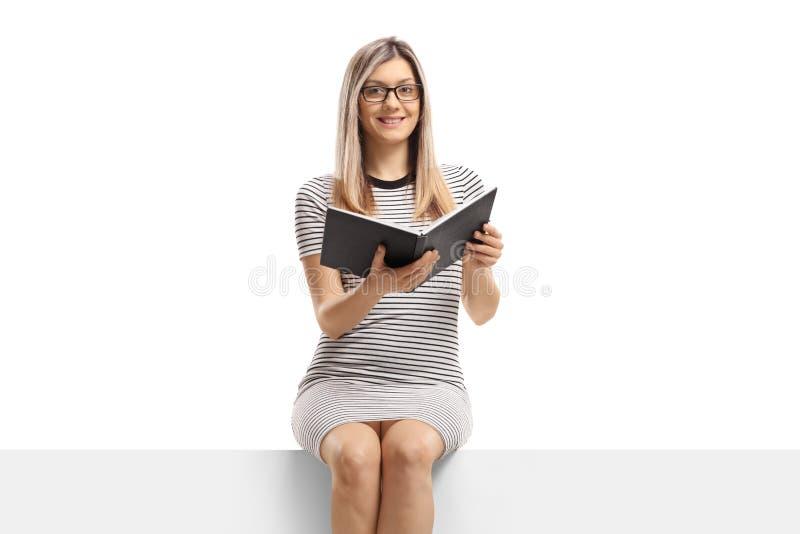 Jonge blonde vrouw die een boek houden en op een paneel zitten stock foto's