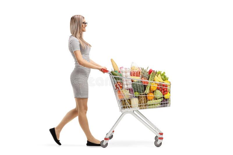 Jonge blonde vrouw die een boodschappenwagentje met voedingsmiddelen en het lopen duwen stock foto