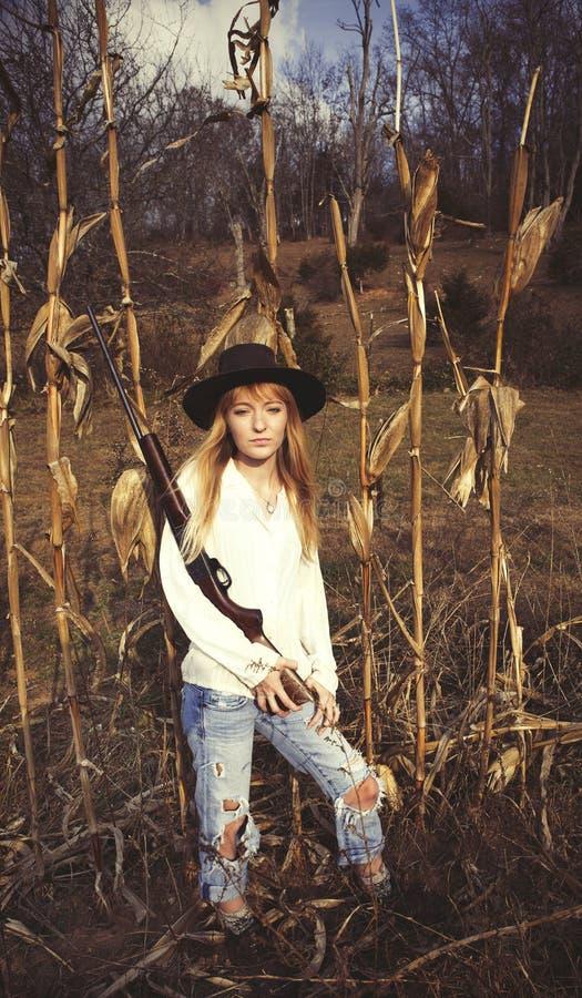 Jonge blonde vrouw die een kanon houden en zich op een graangebied bevinden royalty-vrije stock afbeeldingen