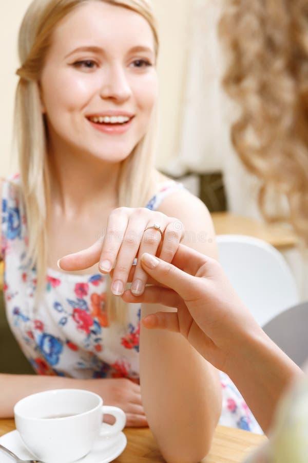 Jonge blonde vrouw die haar trouwring tonen stock foto