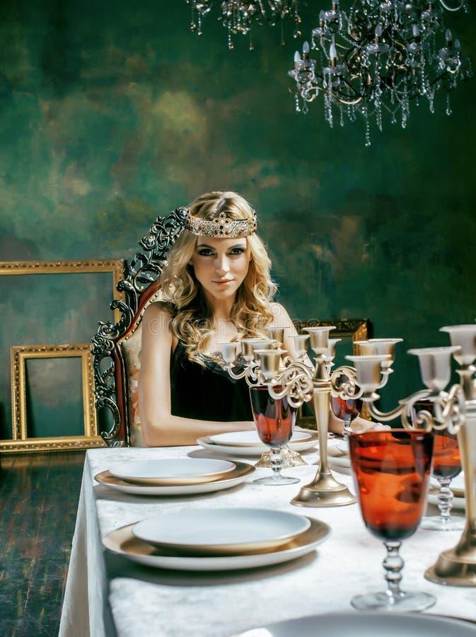 Jonge blonde vrouw die kroon in het binnenland van de feeluxe met em dragen stock afbeeldingen