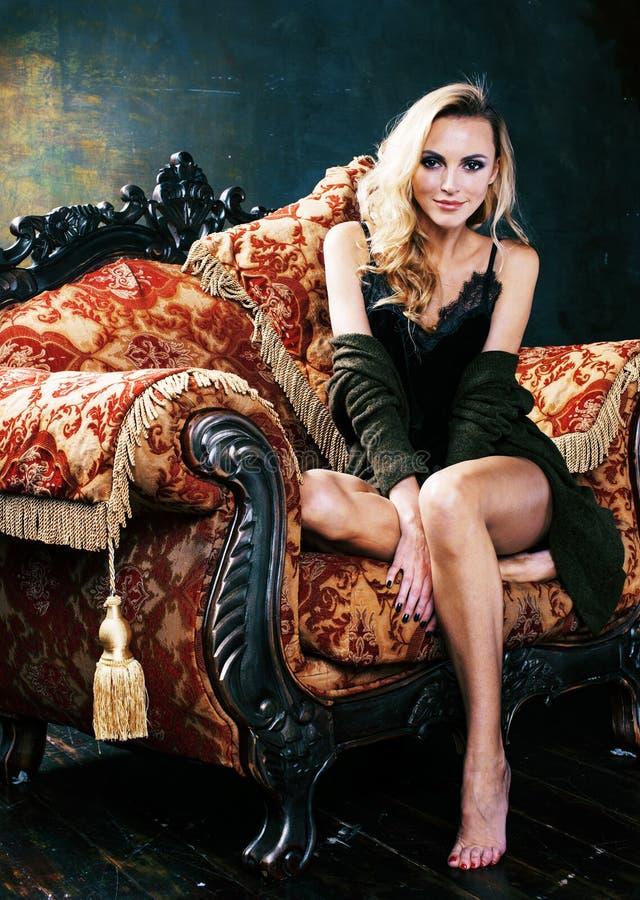 Jonge blonde vrouw die kroon in het binnenland van de feeluxe met em dragen stock foto's