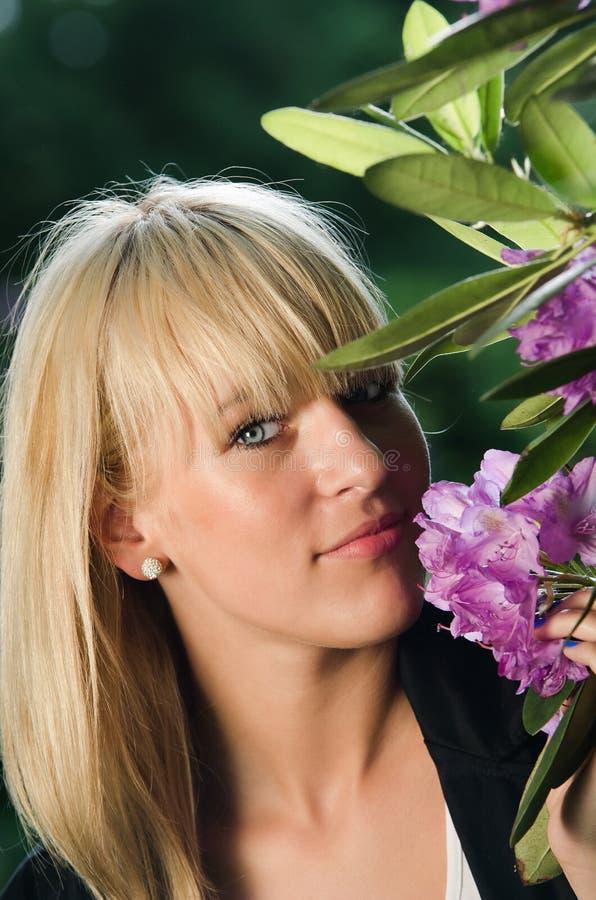 Jonge blonde vrouw die lilac ruikt royalty-vrije stock afbeelding