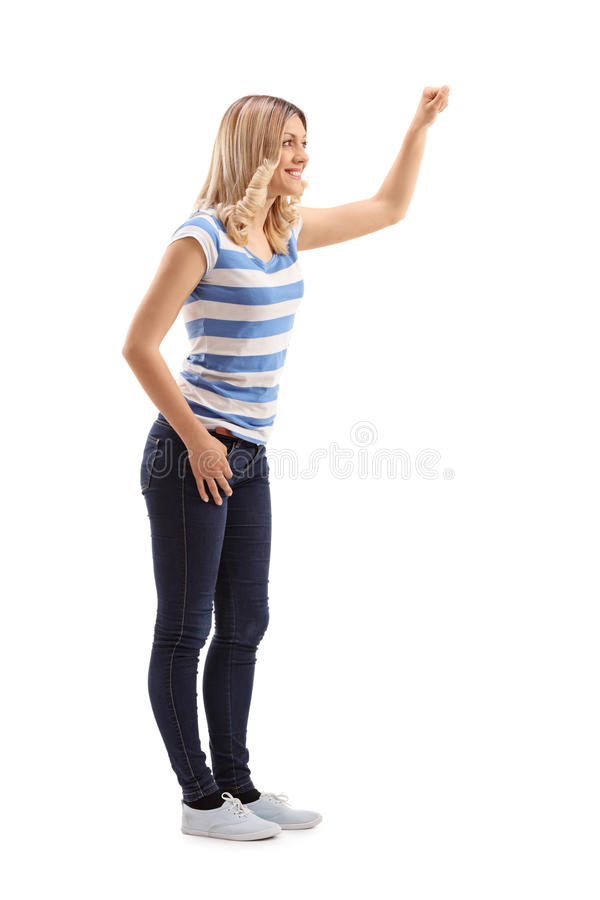 Jonge blonde vrouw die op een deur kloppen stock afbeeldingen