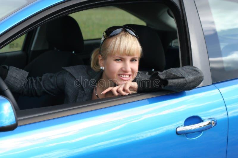Jonge blonde vrouw in een auto. stock afbeelding