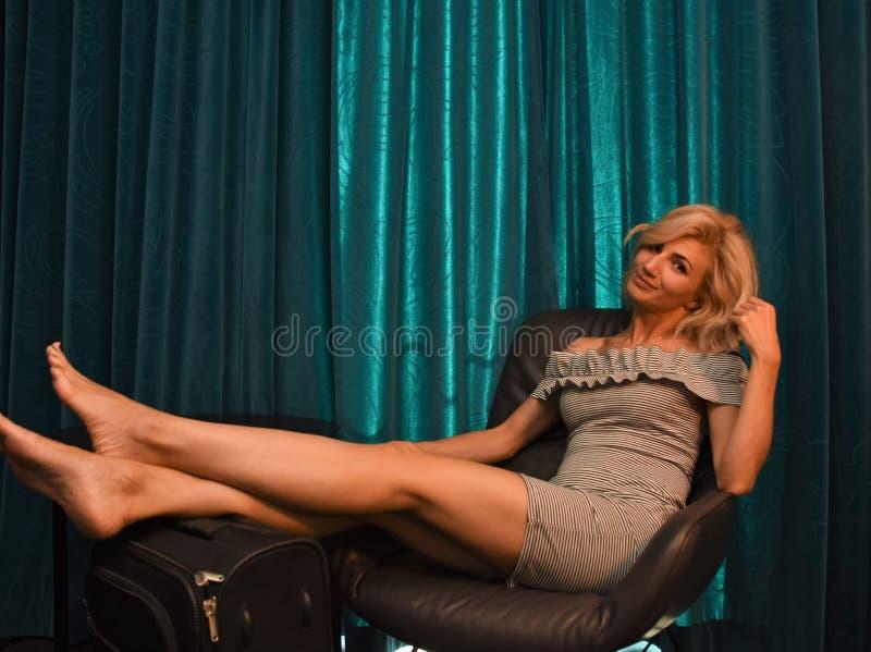 Jonge blonde vrouw in een korte kledingszitting op een stoel royalty-vrije stock afbeeldingen