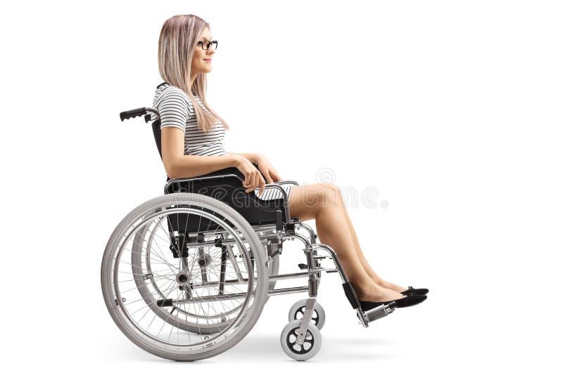 Jonge blonde vrouw in een rolstoel stock foto's