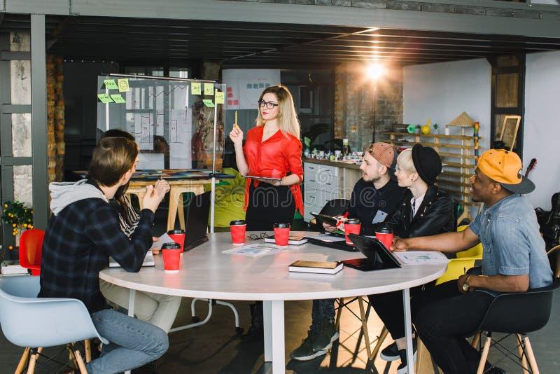 Jonge blonde vrouw in glazen die zich bij glasmuur bevinden in een vergadering met multinationaal team van arbeiders stock afbeeldingen