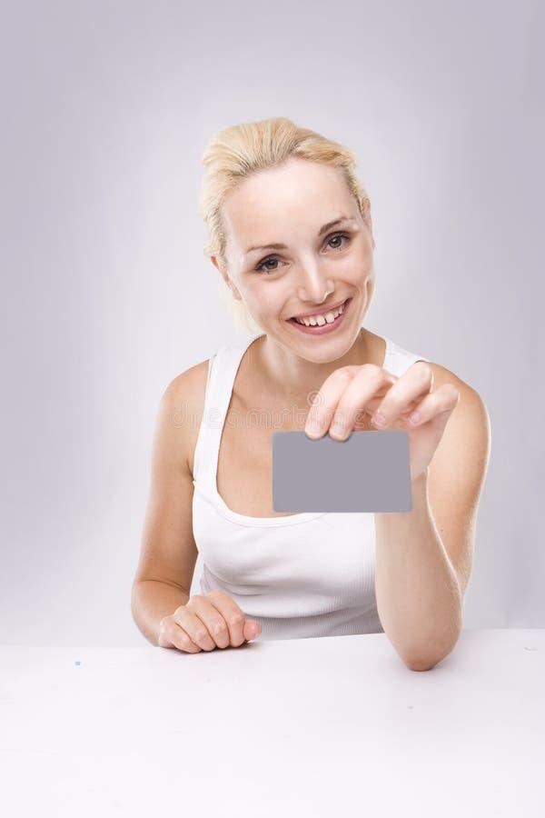 Jonge blonde vrouw met adreskaartje ter beschikking royalty-vrije stock afbeelding