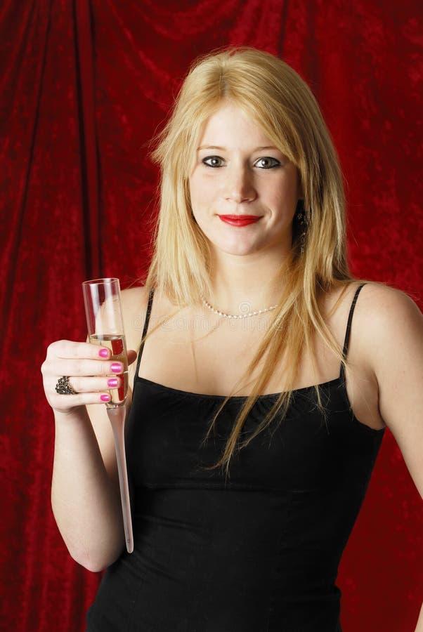 Jonge blonde vrouw met glas champagne op rode B royalty-vrije stock foto's