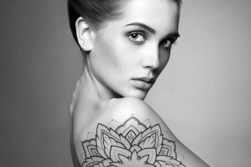 Jonge blonde vrouw met tatoegering stock foto's