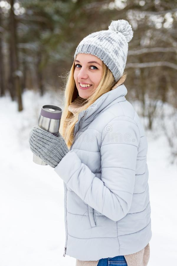Jonge blonde vrouw met thermo cup koffie in winterpark of bos stock foto