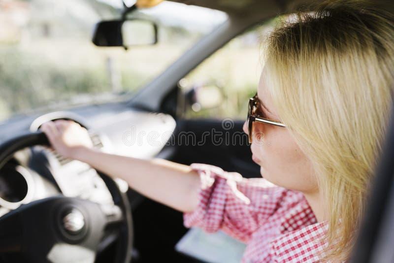 Jonge blonde vrouw met zonnebril die auto drijven stock foto