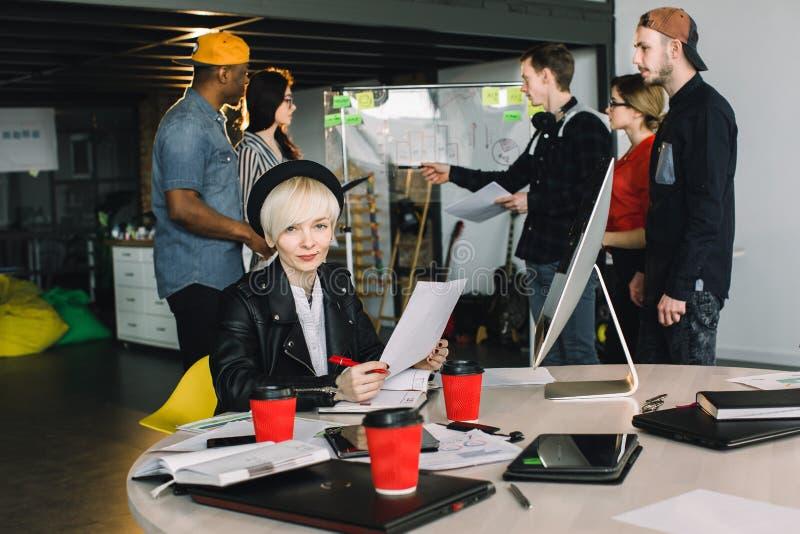 Jonge blonde vrouw in zwarte hoed en vrije tijdsjasjezitting bij de lijst en het werken met documenten Toevallig wijfje en mannet royalty-vrije stock afbeelding
