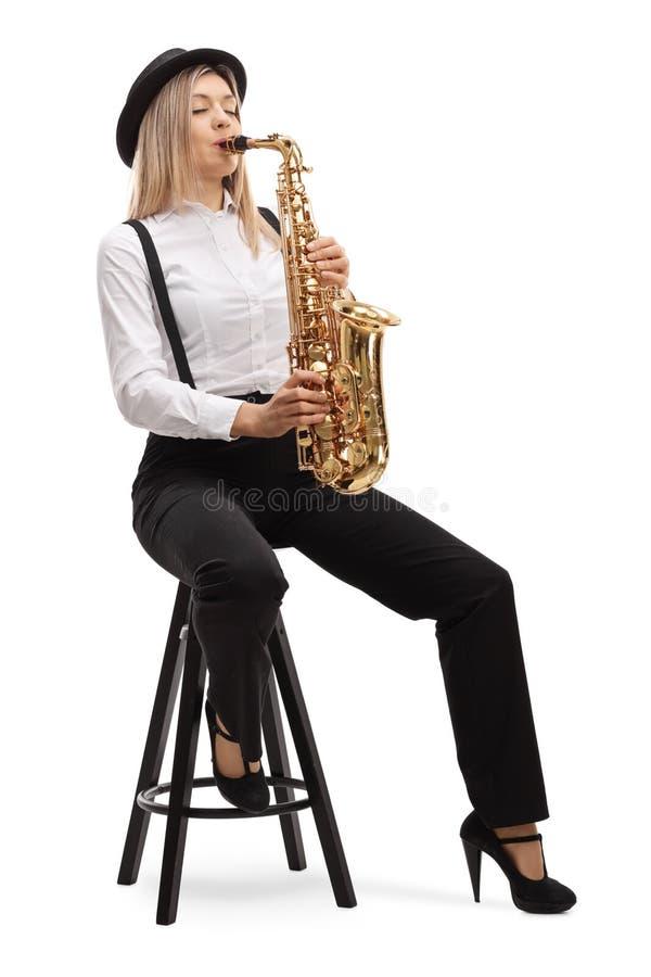 Jonge blonde vrouwelijke kunstenaar die een saxofoon speelt stock foto's