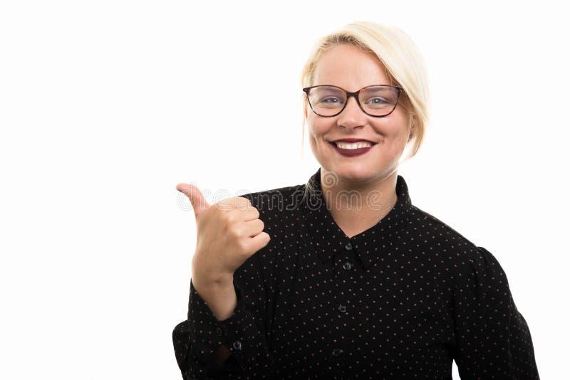 Jonge blonde vrouwelijke leraar die glazen dragen die duim tonen ges stock foto