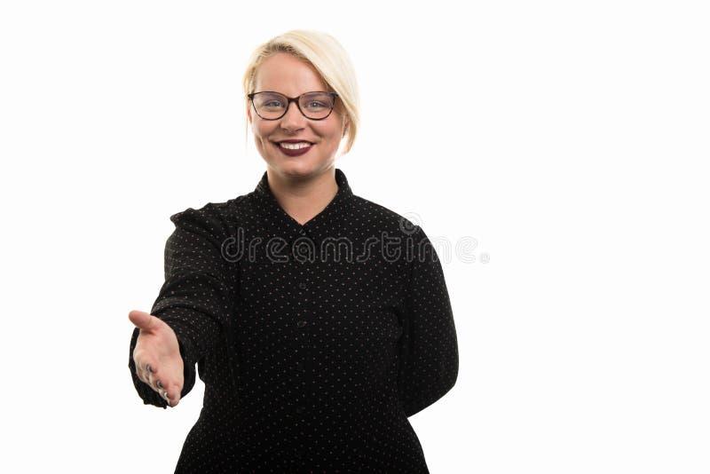 Jonge blonde vrouwelijke leraar die glazen dragen die handdruk g aanbieden stock foto