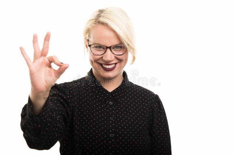 Jonge blonde vrouwelijke leraar die glazen dragen die o.k. gebaar tonen stock afbeelding