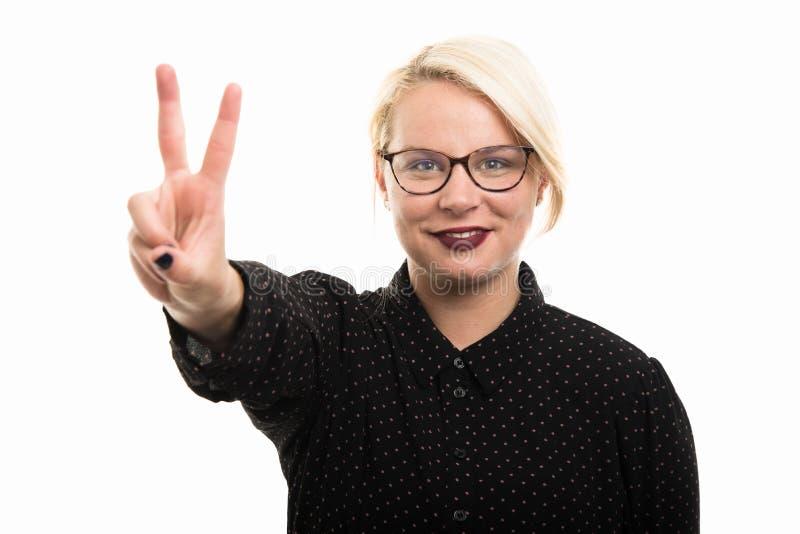 Jonge blonde vrouwelijke leraar die glazen dragen die overwinning tonen gest stock afbeelding