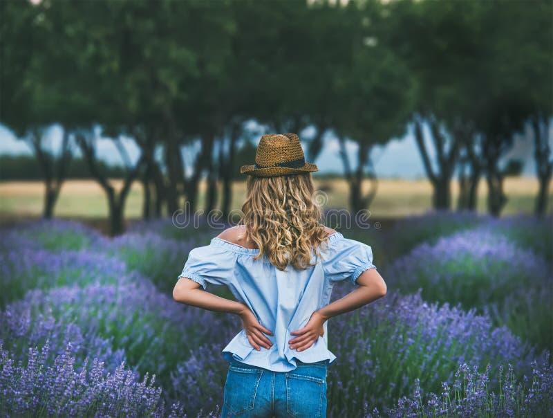 Jonge blonde vrouwenreiziger die zich op lavendelgebied bevinden in Turkije stock afbeelding