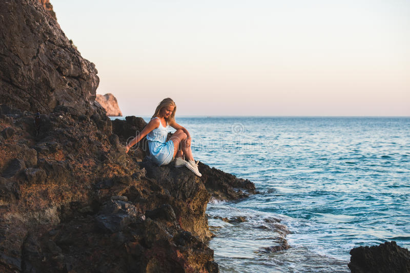 Jonge blonde vrouwentoerist in blauwe kleding sittig op rotsen en het bekijken het overzees Alanya, Mediterraan gebied, Turkije stock afbeelding