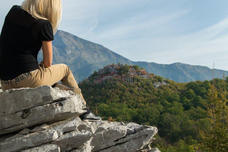 Jonge blonde vrouwenzitting op de rand van de bergklip tegen mooie bergenpiek royalty-vrije stock foto's