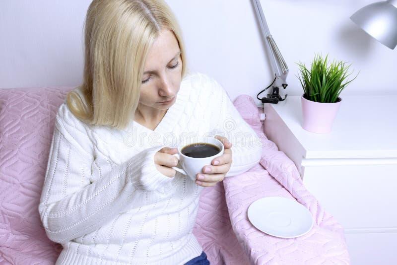 Jonge blonde vrouwenzitting op roze bank en het drinken koffie royalty-vrije stock fotografie