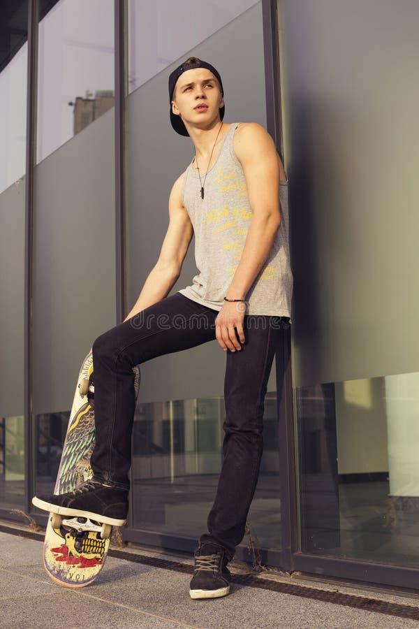 Jonge blondekerel op skateboard in toevallige uitrusting in stedelijk CIT stock foto