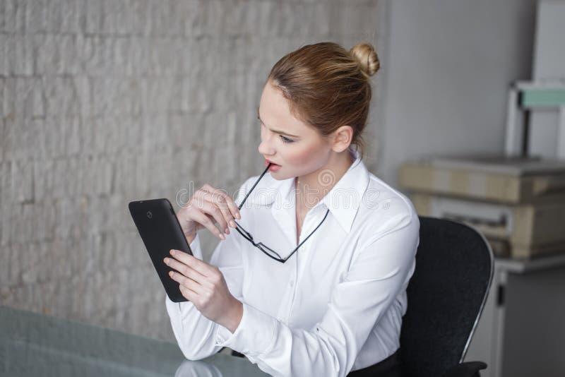 Jonge blondeonderneemster die bizar bericht op tablet lezen royalty-vrije stock afbeeldingen