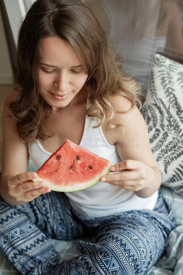 Jonge Blondevrouw in blauwe pyjama's op het bed die een watermel eten royalty-vrije stock afbeelding