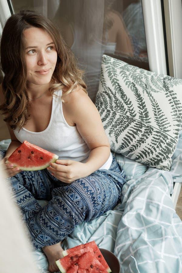 Jonge Blondevrouw in blauwe pyjama's op het bed die een watermel eten stock fotografie