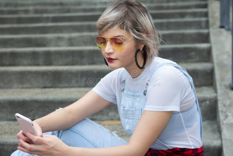 Jonge blondevrouw in de stad die celtelefoon met behulp van royalty-vrije stock afbeeldingen