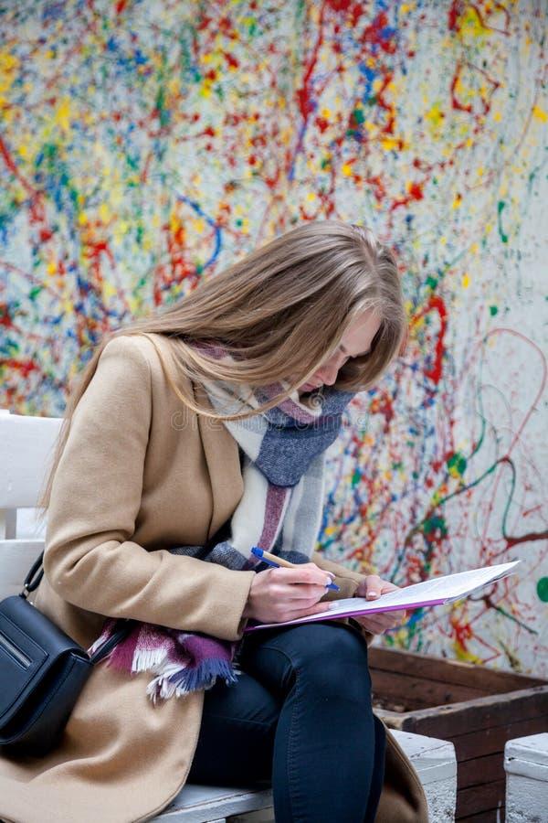 Jonge blondevrouw die bij bank en het schrijven situeren royalty-vrije stock foto