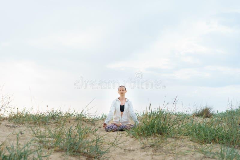 Jonge blondevrouw die de praktijk van de ochtendyoga in openlucht op B doen stock afbeelding