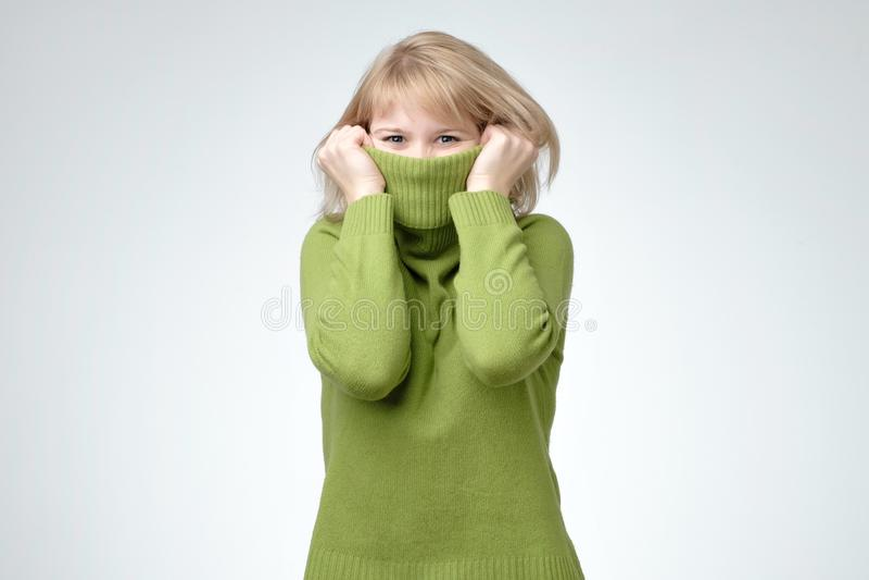 Jonge blondevrouw die een hoge hals groene sweater dragen die haar gezicht verbergen stock afbeelding