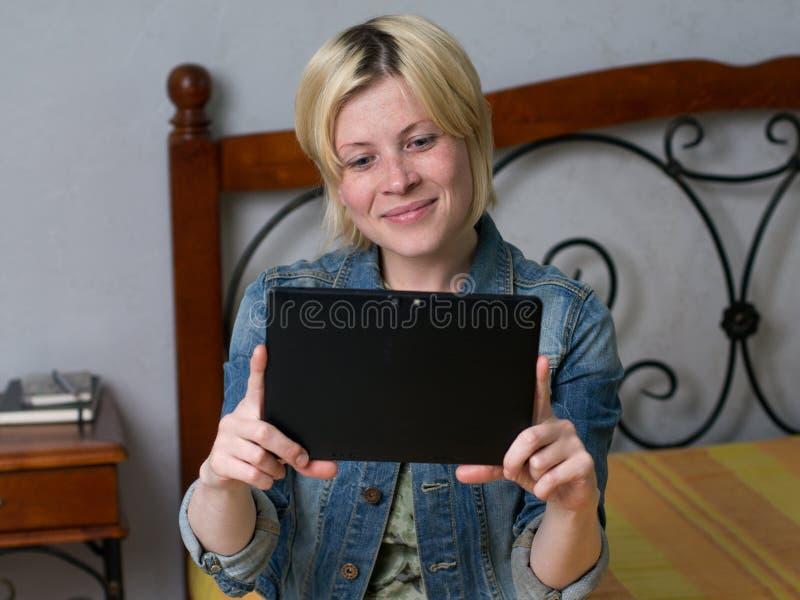 Jonge blondevrouw die een tablet en het glimlachen houden royalty-vrije stock foto's