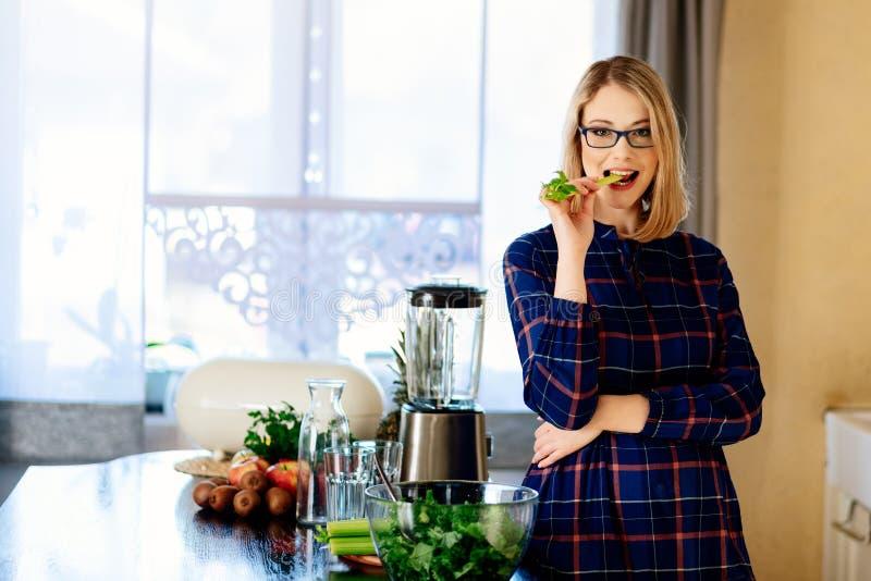 Jonge blondevrouw die groene selderie in keuken eten royalty-vrije stock foto's