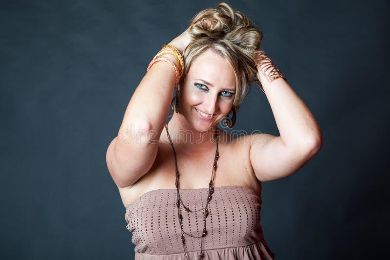 Jonge blondevrouw die haar haar verhogen stock fotografie