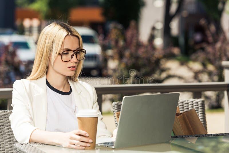 jonge blondevrouw die in oogglazen beschikbare koffiekop houden royalty-vrije stock foto's