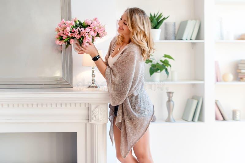 Jonge blondevrouw die ruimte met mooie bloemen verfraaien Mooie vrouw die bloemen schikken en haar verfraaien die leven royalty-vrije stock afbeelding