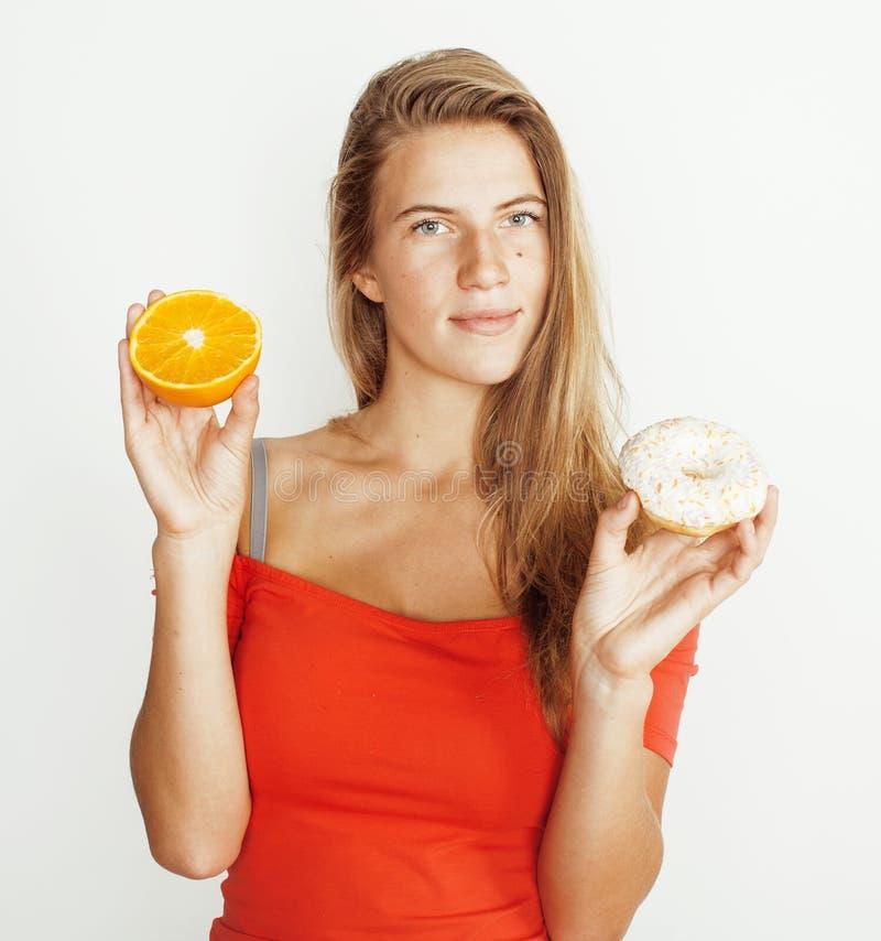 Jonge blondevrouw die tussen doughnut en oranje fruit op witte achtergrond, het concept van levensstijlmensen kiezen stock afbeeldingen